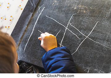 A child's hand drawing on a blackboard with chalk