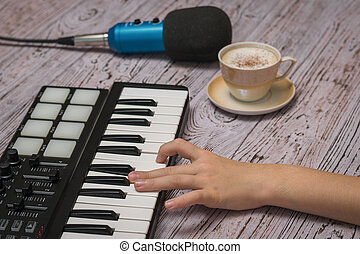 A child's hand on the keys of a music mixer and a Cup of coffee on a wooden table. The process of creating music.