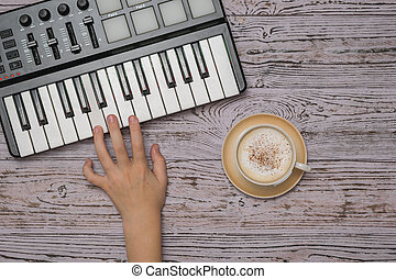 A child's hand on the keys of a music mixer and a Cup of coffee on a wooden table. The process of creating music. The view from the top.