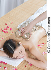 A Chinese medicine cupping of the young lady at spa salon, ...