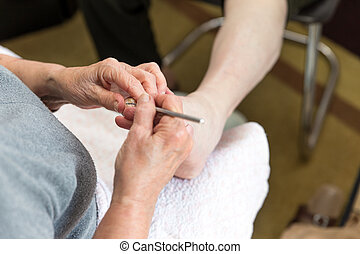 chiropodist at home makes a treatment of the feet