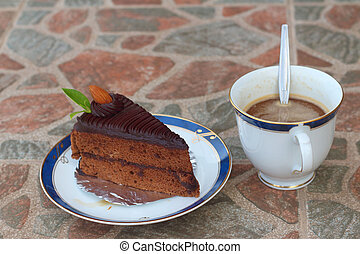 A chocolate cake with a cup of coffee.