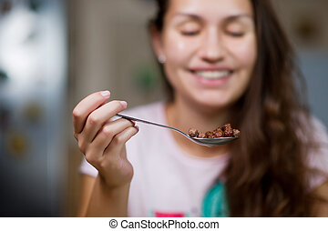 a chocolate cereal and a girl smile in the background