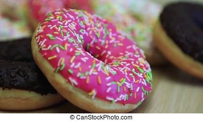 A chocolate donut and a donut in a pink frosting lie on the table. HD