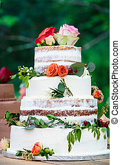 A chocolate wedding cake with white frosting and red, pink, and orange flowers with green leaves - wedding cake series