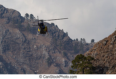 A Chopper flying from between mountain valley in rescue operation concept.