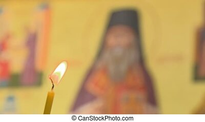 A christian icon St. Theophan the Recluse in front of a candle