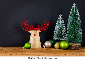 Christmas decoration black background with tree glass balls and wooden reindeer