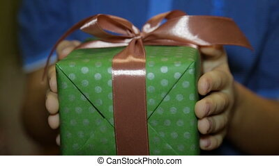 A Christmas gift box in the hands of a child - Christmas...