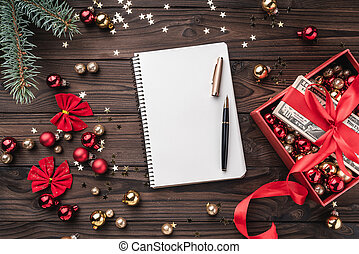 A Christmas gift, money packed with red slack, Xmas items, on a wooden background. Top view. Text space in the notebook.