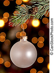 a christmas ornament hanging from a pine branch