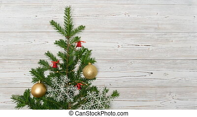 a Christmas tree appears on a light wooden background, decorates and gifts fall from above
