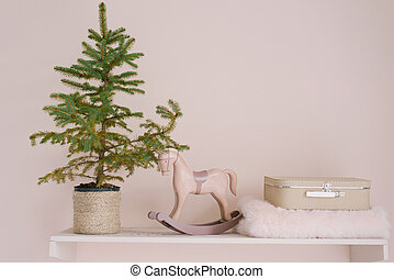 A Christmas tree in a wicker pot stands on a shelf, next to a wooden retro toy rocking horse, a small suitcase and a blanket. Decor for Christmas and New Year in the living room or children's room