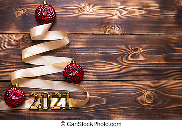 A Christmas tree made of gold ribbon with the numbers 2021 is decorated with red balloons on a dark wooden background. Flat lay. Space for text. New year, Santa hat.