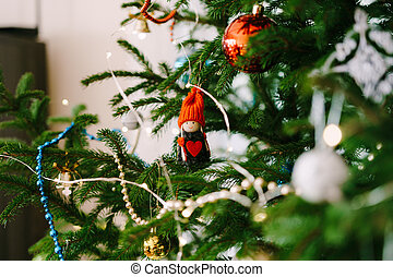 A Christmas tree toy on the branches of a tree - a little girl in a red hat with a big red heart.