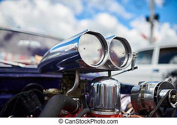 A chrome supercharger on an old car, against the sky.