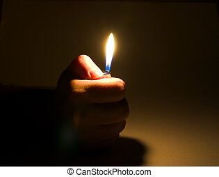 a cigarette-lighter in a hand burns on a dark background