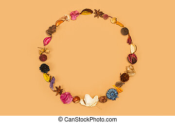 A circle made with dry flowers and leaves on a brown background