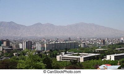 A city near the mountains - A panning, hand held, wide shot...