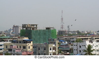 An establishing shot of a cityscape with tall buildings and network masts in Myanmar