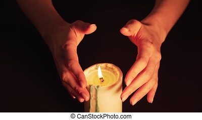 A clairvoyant witch guesses over a candle. Women's hands over the flame are isolated on a black background. The concept of paranormal, prediction of the future and mysticism 4k