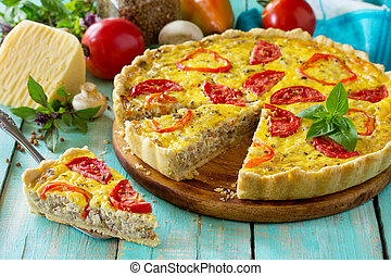 A classic quiche Lorraine pie with buckwheat, mushrooms, paprika, tomatoes, cheese and egg filling on a wooden table.