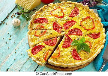 A classic quiche Lorraine pie with buckwheat, mushrooms, paprika, tomatoes, cheese and egg filling on a wooden table. Copy space.