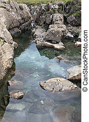 A clear pool with a rocky bottom on a cloudy day