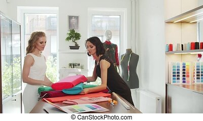 A client and a seamstress choose a fabrics in a tailor shop...