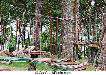 A climbing wall, trolls and a rope park are sporting for games and entertainment from boards and trees with ropes for playing children and adults in the woods in nature