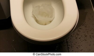 Clogged ceramic white bowl toilet with paper close up view. Water spreading on the floor