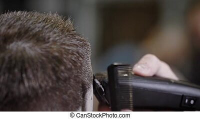 A close shot at the process of trimming hair with a hair clipper, the hairdresser uses a comb to help create a hairstyle