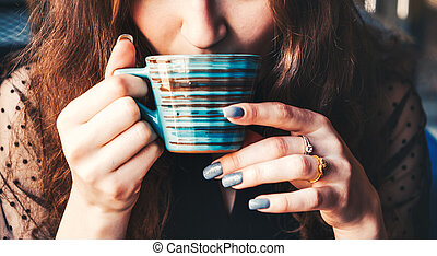A close shot of a girl's face drinking tea from a striped ceramic cup. We only see the part of her face and her hands holding a mug with a hot drink.