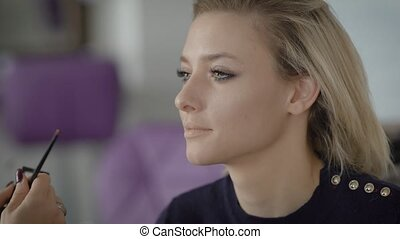 A close shot of a young girl's face that is applied makeup on the face with the help of professional brushes, sponge. Make-up artist creates shadows brown eyebrows for eyebrows, making them thicker