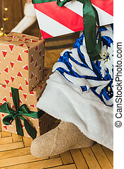 A close shot of the boots of Father Frost. Santa Claus in a blue fur coat sits in the Christmas interior against the background of a Christmas tree