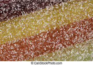 A close up abstract macro photo of a sugar coated multi coloured jelly fruit sweet.