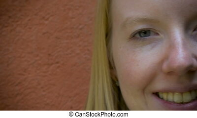 A close up dolly shot portrait of a young woman smiling at the camera