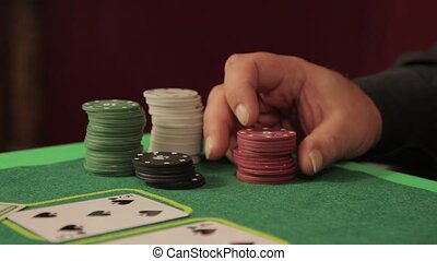 A close-up hand at the gambling table goes through the chips
