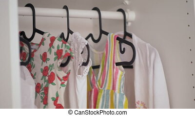 A close up of a baby girl clothes hanging in a wardrobe - A...