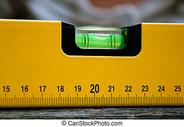 A close-up of a builders spirit level on a wooden surface