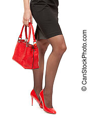 A close-up of a chic red handbag along with sexy female legs wearing elegant red shoes. Isolate on white.