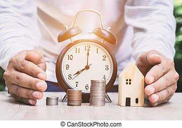 A close-up of a man hand around a house, money and a watch, with a green bokeh background, money saving concept to prepare for the future.
