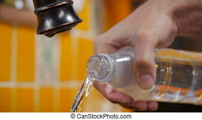 A close up of a man pouring water out of a plastic bottle