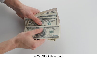 A close-up of a man's hand count money and give it to another person. The concept of wages