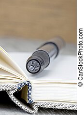A close up of a pen lying on an open journal diary notebook