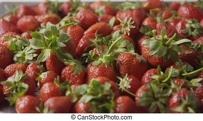 A close-up of a red ripe juicy strawberry slow falls one by ...