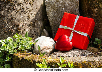close up of a rockery with a red heart and a gift