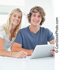 A close up of a smiling couple holding a tablet and looking at the camera