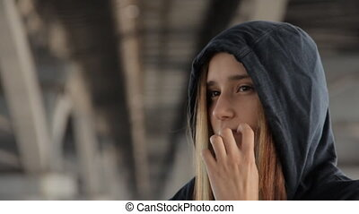 A close up of a teenage girl in a hoody with the hood on and loose multicolored hair spread in the wind under the unfocused bridge pillars scratching a cheek.