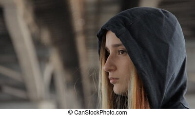 A close up of a teenage girl in a hoody with the hood on and loose multicolored hair spread in the wind under the bridge pillars.